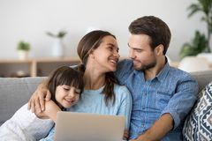 Diverse family spend free time at home using laptop. Multi-ethnic young married couple and little adorable daughter sitting on sofa at home spend free time on stock illustration