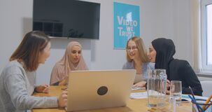 Diverse female colleagues at office hijab asian negotiation discussion watching funny video