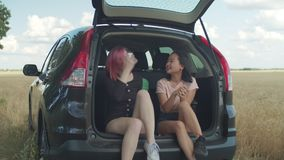 Diverse females enjoying leisure during road trip. Beautiful multiracial female friends chatting and enjoying outdoor leisure while sitting in car trunk during stock footage