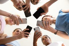 Diverse females standing in circle holding smartphones view from stock image