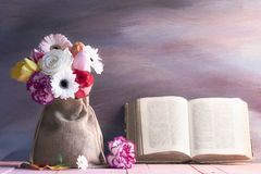 Diverse flower bouquet and an old open book Royalty Free Stock Photos