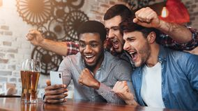 Diverse football fans watching football on smartphoner in pub. Diverse football fans watching football on smartphone and celebrating victory score in pub stock photography