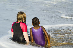 Diverse friends. Two children, black and white, playing together in the sea Stock Images