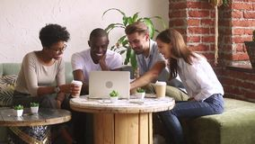Diverse friends enjoy time in cafe watching movie on computer