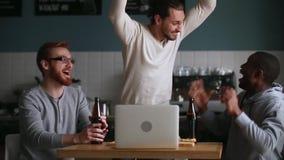 Diverse friends hangout in pub watching online match at laptop
