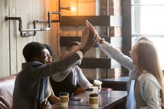 Diverse friends join hands together giving high-five at cafe mee. Excited diverse friends join hands up together at cafe meeting, happy multiracial young people stock image