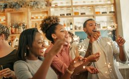 Diverse friends laughing and celebrating with sparklers in a bar royalty free stock photos