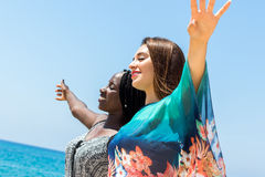 Diverse friends with open arms outdoors. Royalty Free Stock Photography