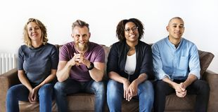 Diverse friends sitting together on couch Royalty Free Stock Images