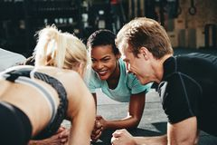 Diverse friends smiling while planking together during a gym wor. Smiling group of diverse friends in sportswear planking together on the floor of a gym during a stock photo