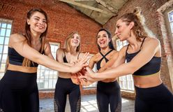 Diverse funny girls together in circle on rubber mats wearing sportswear smiling show yoga greeting gesture, looking at stock images