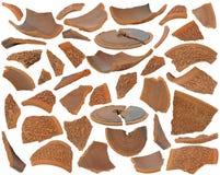Diverse gebroken bruine ceramische scherven bij diverse hoeken op witte B Royalty-vrije Stock Afbeelding