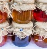 Diverse gekleurde honingskruiken met stof op deksel royalty-vrije stock afbeelding