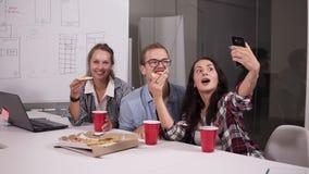 Diverse gelukkige medewerkers die pizza eten tijdens onderbreking in bureau en selfie gelukkig allen nemen samen Modern, helder stock video