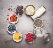 Diverse Gezonde ontbijtingrediënten met superfood: chiazaden, gojibessen, havermeel, verse bessen, honing en melk of yoghurt stock foto