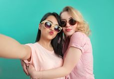 Diverse girls in casual outfits shooting selfie isolated on blue background. stock photos