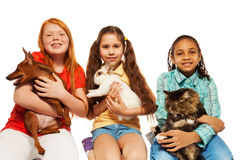 Diverse girls playing with their pets together. Hugging cat, dog and rabbit isolated on white Stock Photography