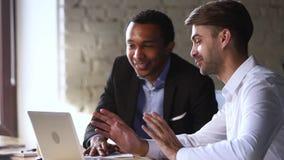 Diverse glimlachende manager en cliënt die vriendschappelijk gesprek met laptop hebben stock footage