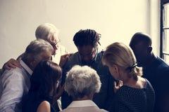 Diverse godsdienstige mensen die samen bidden stock afbeelding