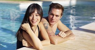 Diverse good looking couple stand in swimming pool stock video