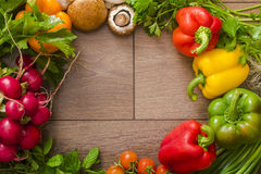 Diverse groenten in een cirkel op de houten vloer Stock Fotografie