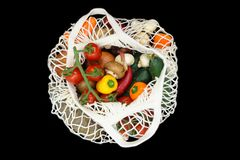Diverse groenten in witte netwerk netto zak en geïsoleerd op zwarte achtergrond royalty-vrije stock foto's