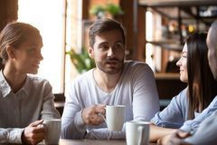 Diverse group of best friends sitting in cafe and chatting. Multi-ethnic group of best friends millennial girls and guys chatting sitting in cafe, employees royalty free stock photos