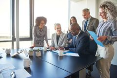 Diverse group of executives working together around a boardroom. Diverse group of businesspeople standing around their manager sitting at an office boardroom stock images