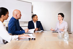 Diverse group of businesspersons conducting an important business meeting Stock Image