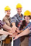 Diverse group of construction workers stacking hands. Isolated on white royalty free stock photo
