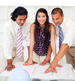 A diverse group of engineers reviewing blueprints Stock Images