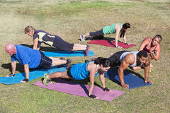 Diverse Group Exercising Outdoors. Diverse group of adults in boot camp fitness class Stock Image