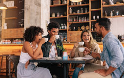 Diverse group of friends enjoying coffee together. Diverse group of friends enjoying some coffee together in a restaurant and talking. Young people sitting stock images