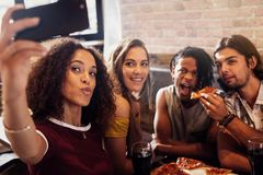 Diverse group of friends enjoying meal and taking selfie. Woman taking selfie with friends eating pizza at a restaurant. Diverse group of men and women enjoying stock image