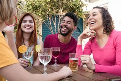 Diverse group of friends having fun at cafe bar outdoor. Group of happy smiling people cheering and drinking together at restaurant outside. Diverse group of royalty free stock photography