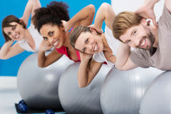 Diverse group of friends having fun at the gym. Diverse group of young riends having fun at the gym working out with gym balls doing Pilates Royalty Free Stock Images
