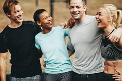 Diverse group of friends laughing after a workout session