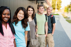 Diverse group of friends in a line. Diverse groiup of friends in a line smiling Stock Photography