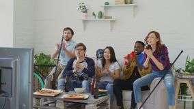 Diverse group of friends sport fans with French national flags watching winter sports games on TV together cheering up. Favourite team at home indoors stock video