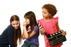 Diverse group of girl actors. Diverse group of girls with one whispering and other holding film slate Royalty Free Stock Image