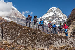 Diverse Group of Hikers staying on Rock in Himalaya Mountains. Diverse Group of Hikers male and female young and mature staying on Rock holding Backpacks and Stock Photography