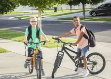 Diverse group of kids riding their bikes to school together. Two diverse boys riding their bikes to school together on the first day of school. Cute kids wearing Royalty Free Stock Photo