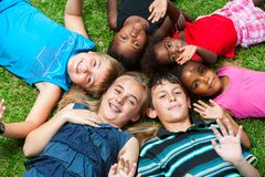 Diverse group og children laying together on grass. Diverse multiracial group of kids laying together joining heads royalty free stock photos