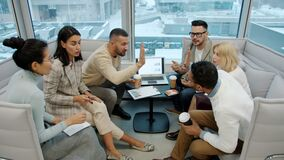Diverse group of people colleagues talking doing high-five in open space office