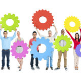 Diverse Group People Holding Gear Teamwork Concept Royalty Free Stock Photos