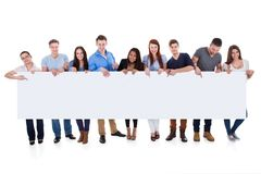 Diverse group of people presenting banner. Isolated on white Royalty Free Stock Photography