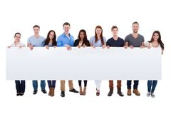 Diverse group of people presenting banner. Isolated on white Royalty Free Stock Images