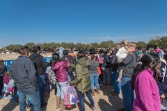 Diverse group of people queue in line to attend outdoor winter festival activities stock photo