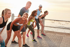 Diverse group of people running together. Shot of athletes at the starting point of a marathon. Diverse group of people running together on seaside promenade Royalty Free Stock Images