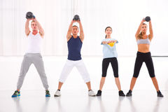 Diverse group practicing kettlebell exercise in crossfit gym Royalty Free Stock Images
